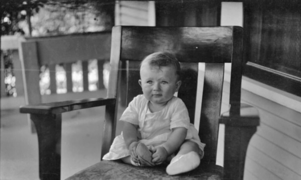 An American baby sitting on a cushioned porch chair (circa 1920s to 1930s).