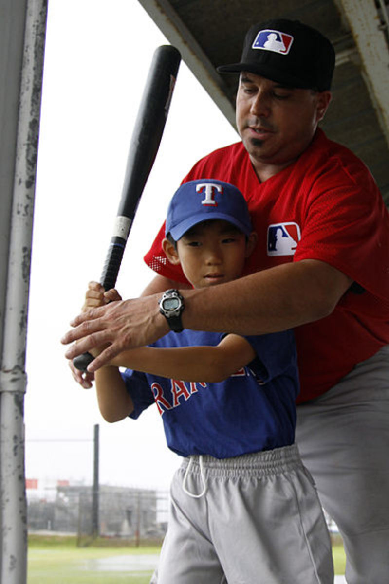 A coach working with a Little League player