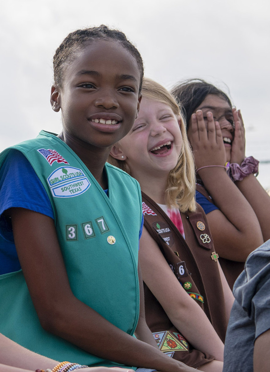 You can see the American flag, council emblem, troop numbers, and membership star on the right side of this Junior's vest. The Brownie beside her has these patches placed the same way, plus the felt tab on the left side of her vest.