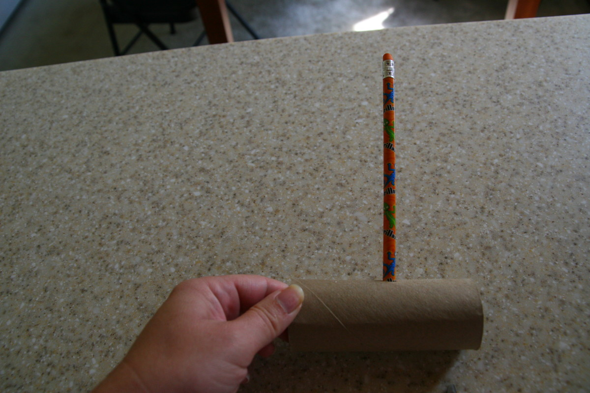 Use a pencil to make a hole halfway down the length of the cardboard tube.