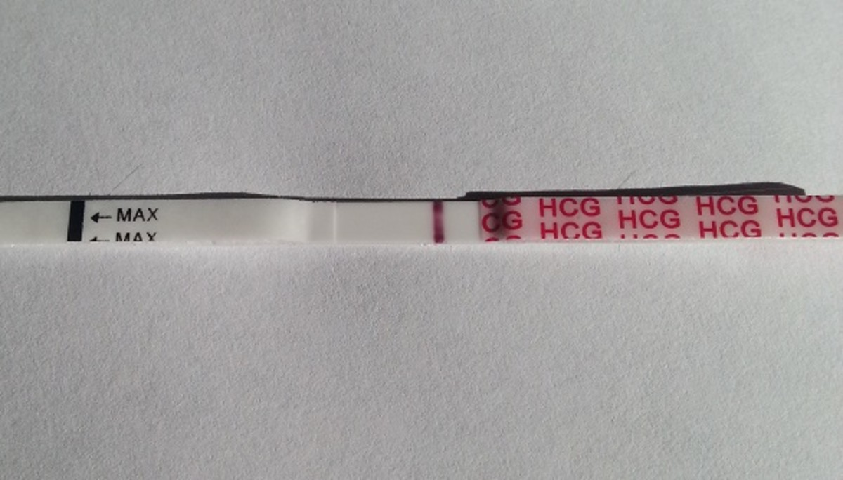 A negative result on a pink-handled Wondfo Dip, one of the cheapest early result pregnancy tests.