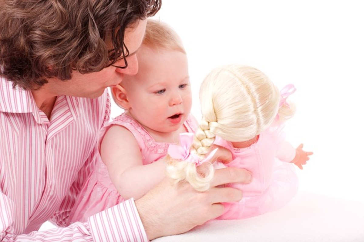 A parent and little baby wearing a pink dress, playing with a pink doll.