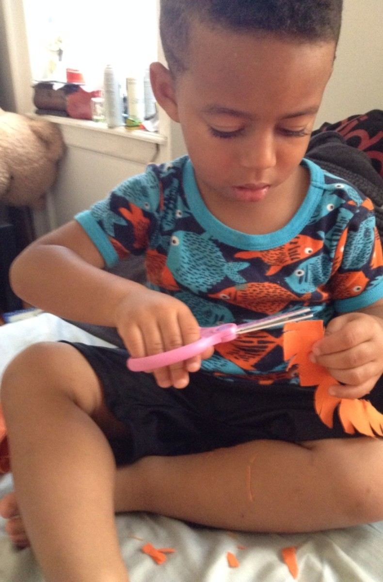 Another option is to let your little one cut up strips of scrap fabric for collage pieces.  Snipping at fabric kept Julian entertained for a good 20 minutes.  Take care that your child knows how to handle scissors first.
