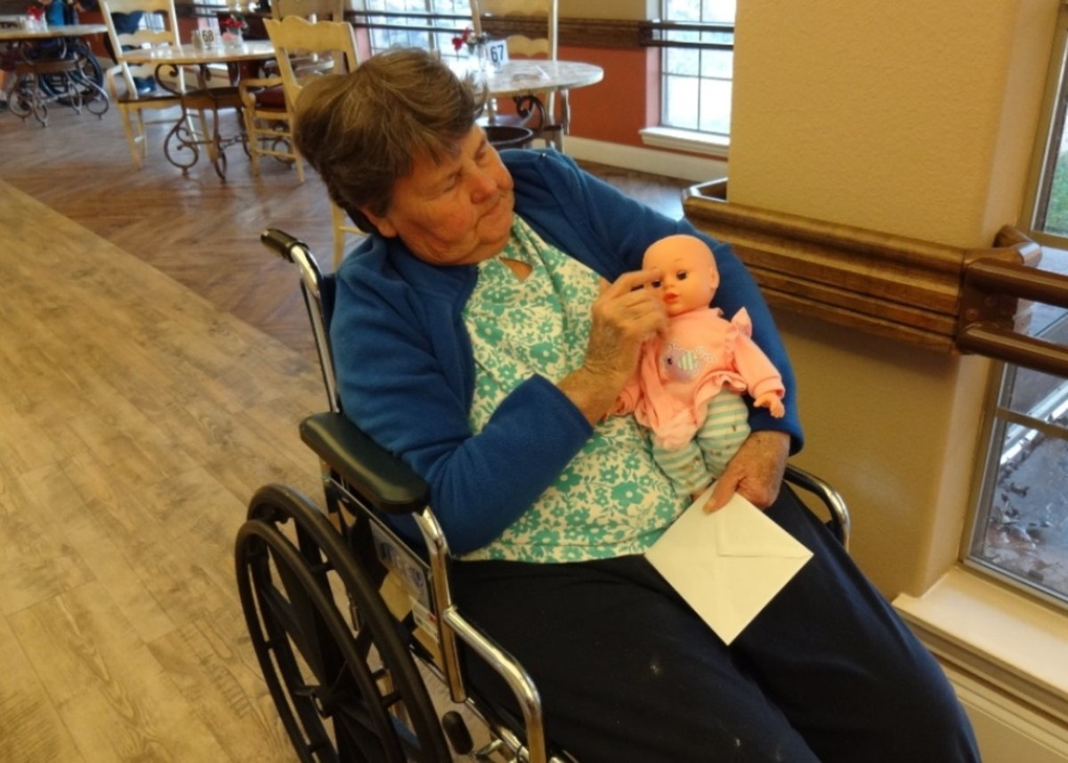 This nursing home resident carries her baby with her during her rounds at the facility.