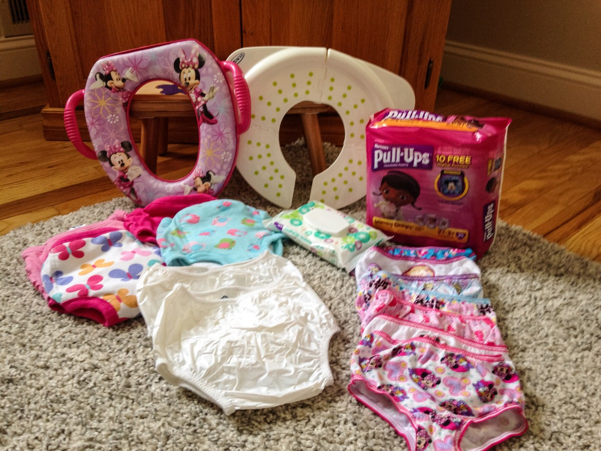 A shot of everything I purchased before potty training; potty seat, folding potty seat, 1 package of Pull Ups, Gerber training pants, flushable toddler wipes, plastic pants, and plenty of underwear.