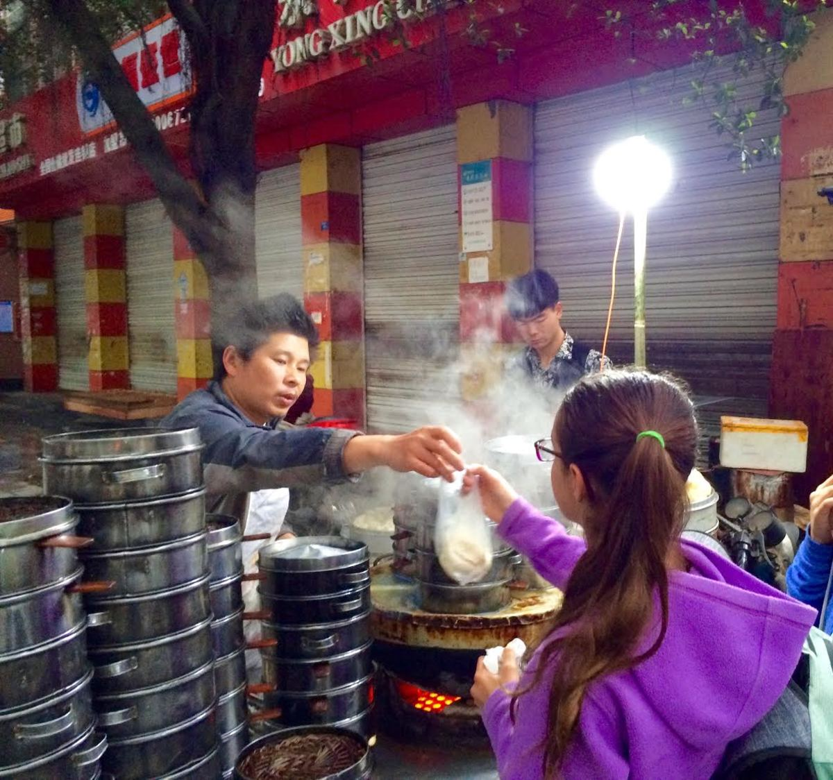 Our daughter orders breakfast from a street vendor in Chengdu, Sichuan Province