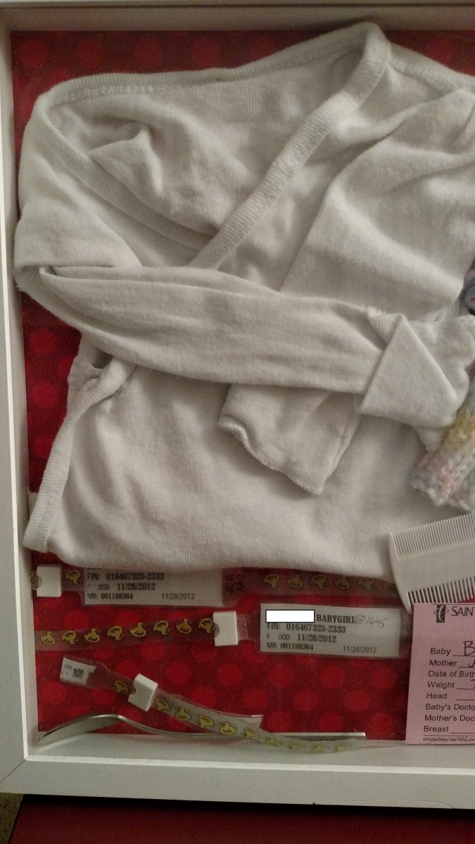 Hospital gown, wrist bands, and comb included in this shadow box detail