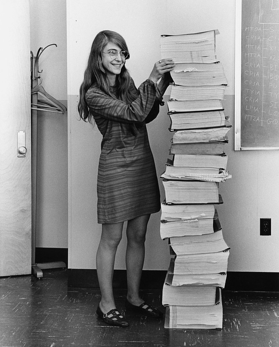 Hamilton in 1969, standing next to a stack of navigation software that she and her MIT team produced for the Apollo project.