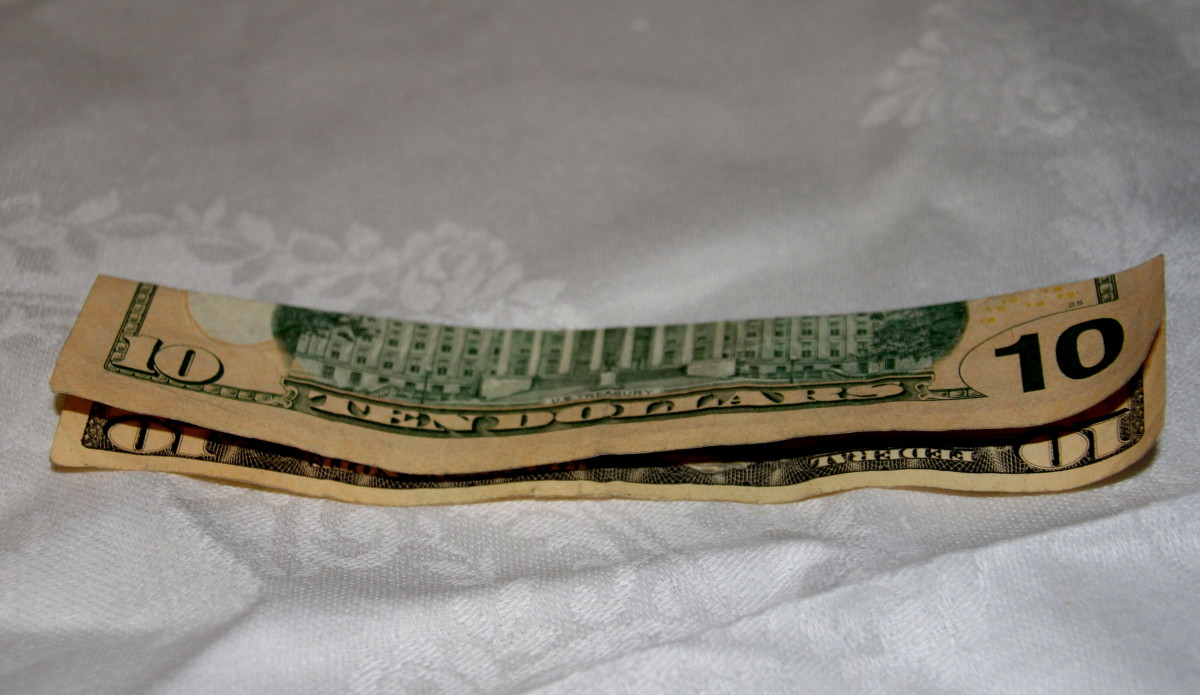 Ten dollar bills are folded with long sides together.