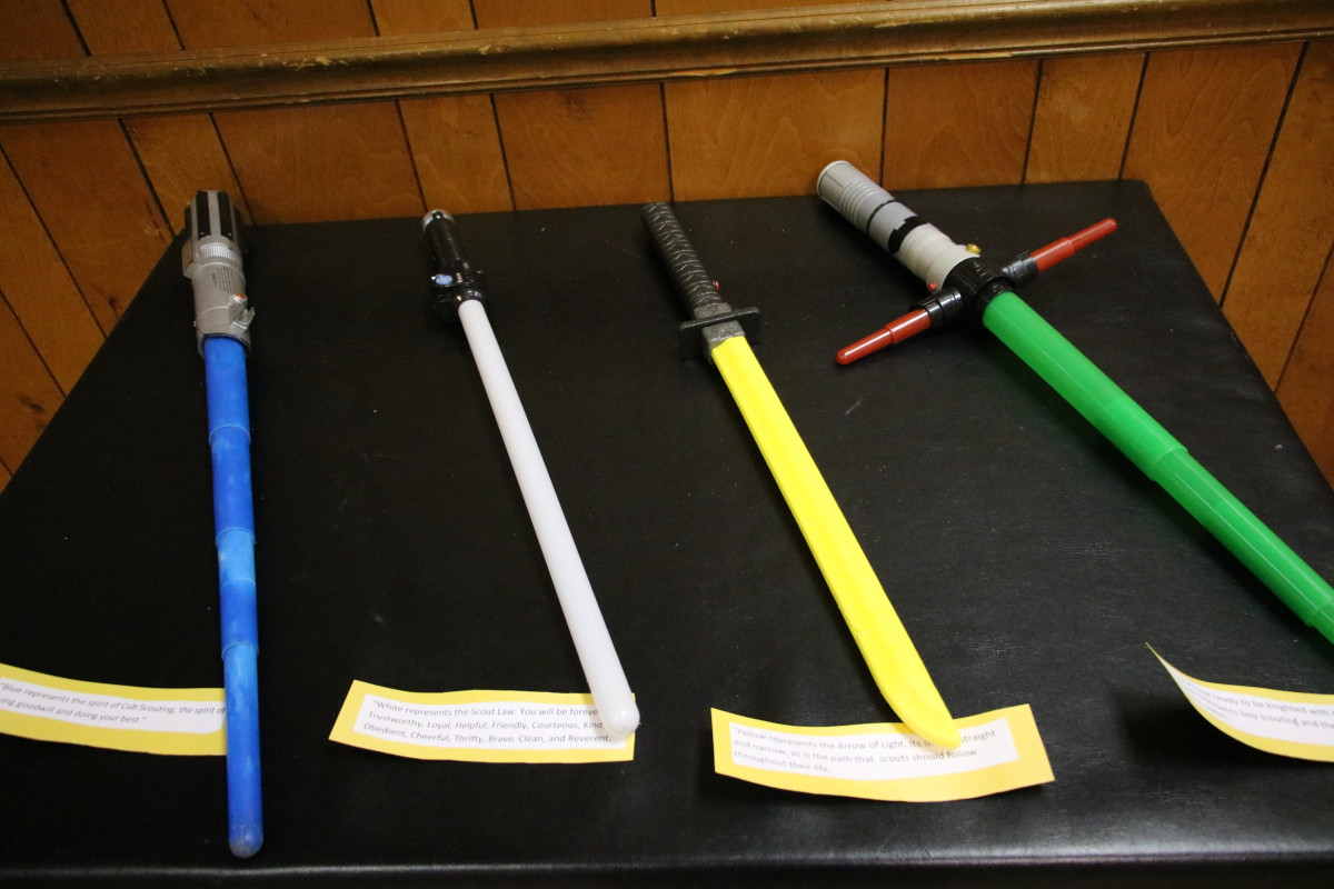 Set out the blue, white, yellow, and green light sabers on a table so they are easily obtained for the Arrow of Light ceremony. Print scripted lines on card stock for adult volunteers to read.