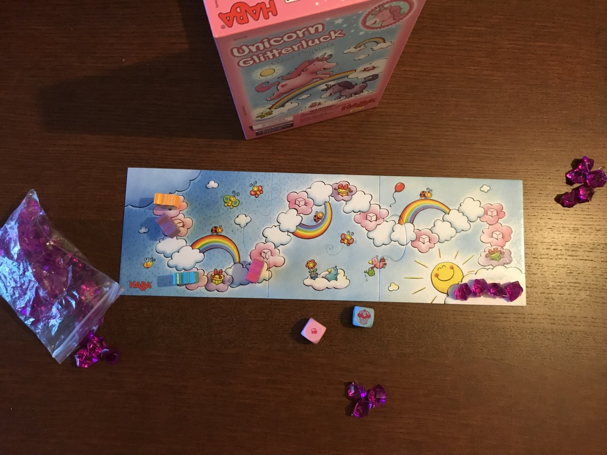 This is the board for Unicorn Glitterluck, showing the cloud course and the different types of clouds. The translucent purple gems are the cloud crystals. The blue die has rolled the dreaded muffin!