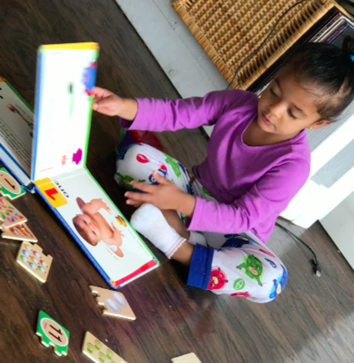 "Free explore time is critical in developing curiosity, independent thinking, and a love of learning. Today, Zoe chose reading a number book to ""help her"" with her number puzzles."