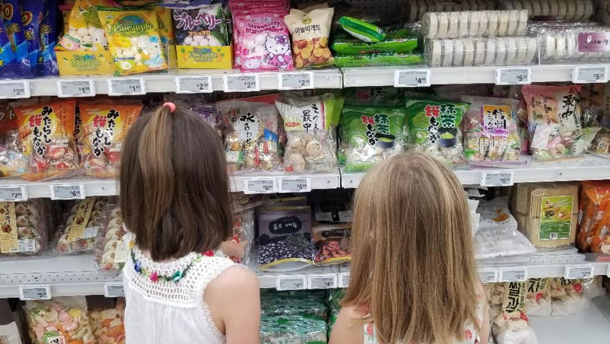 My girls explore the colorful packages in the snack aisle of Zion Market