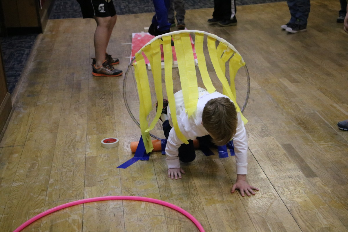 """Create a """"fiery"""" ring in your obstacle course using party streamers and a hula hoop. Obstacle courses can be created indoors for parties that occur during winter months!"""