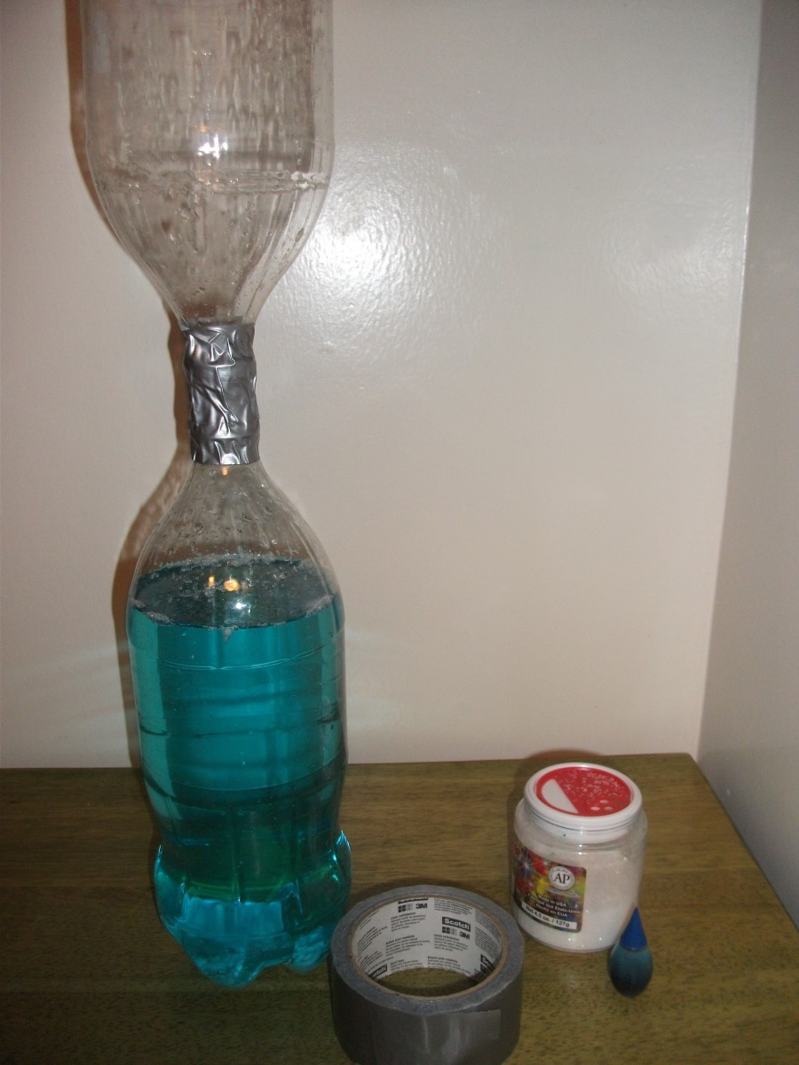 The materials for a tornado experiment: 2 bottles, tape, glitter, and food coloring.