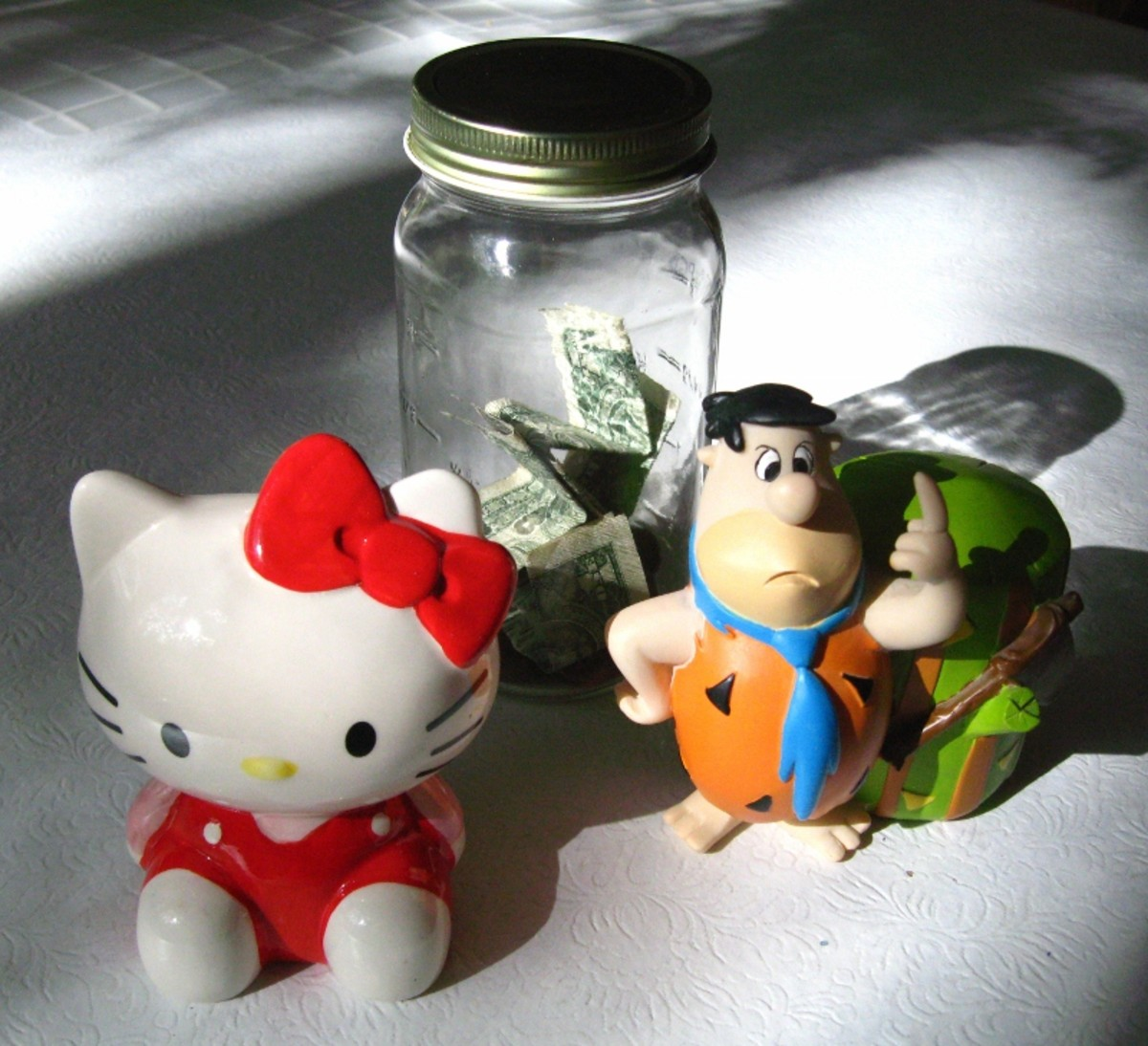 Start saving early. A budget can help save enough money for the things we want to buy.  - Photo: three different piggy banks.