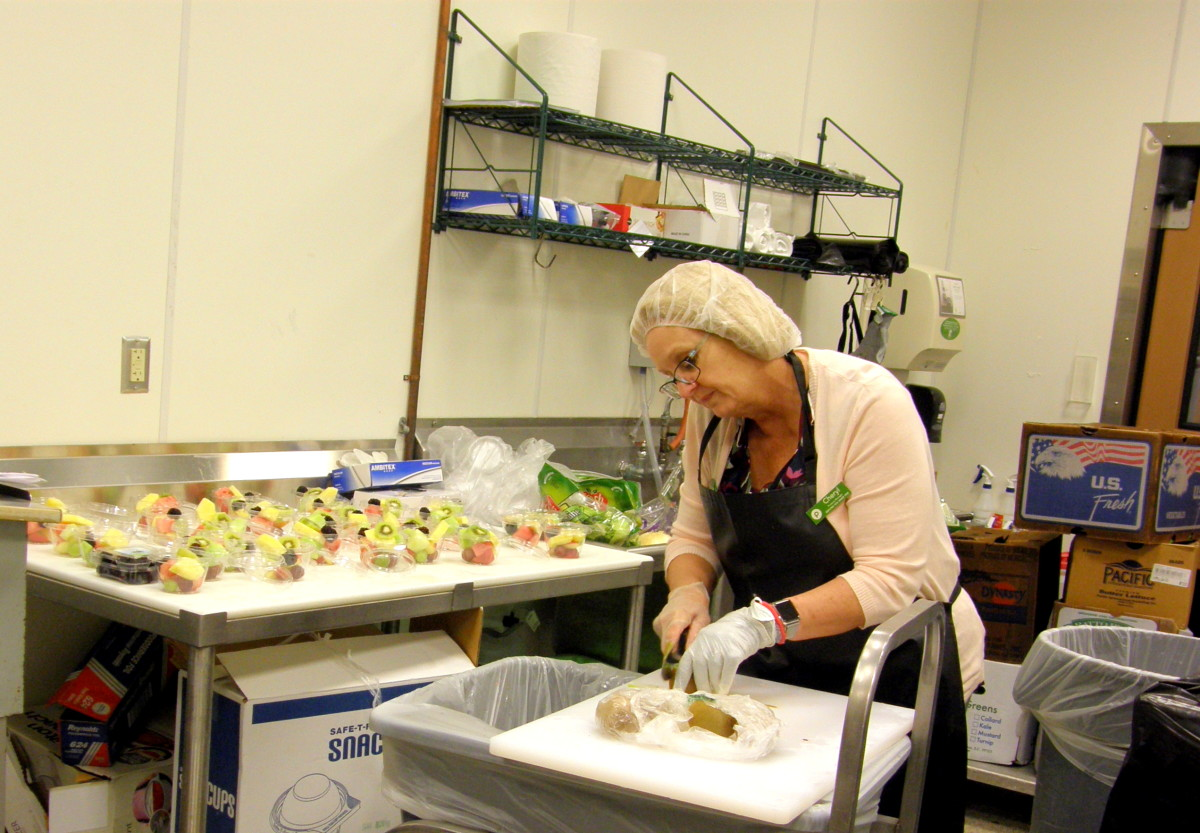 Produce manager prepares fruit cups for all the parents and children on the field trip.