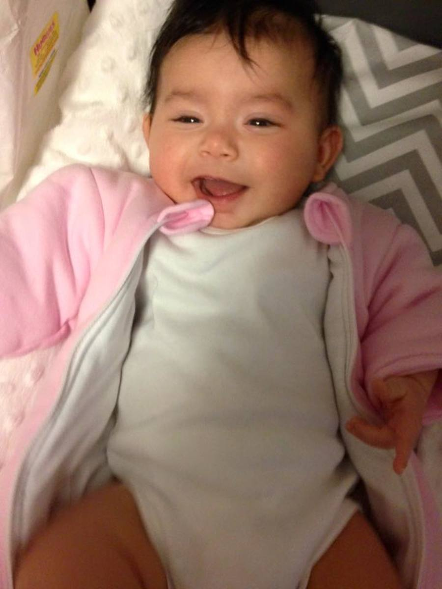 Baby Eva waking up well rested and happy after a night in the Magic Sleepsuit.