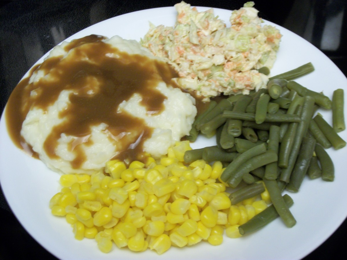 Vegetable plate with potatoes and gravy, corn, green beans and slaw
