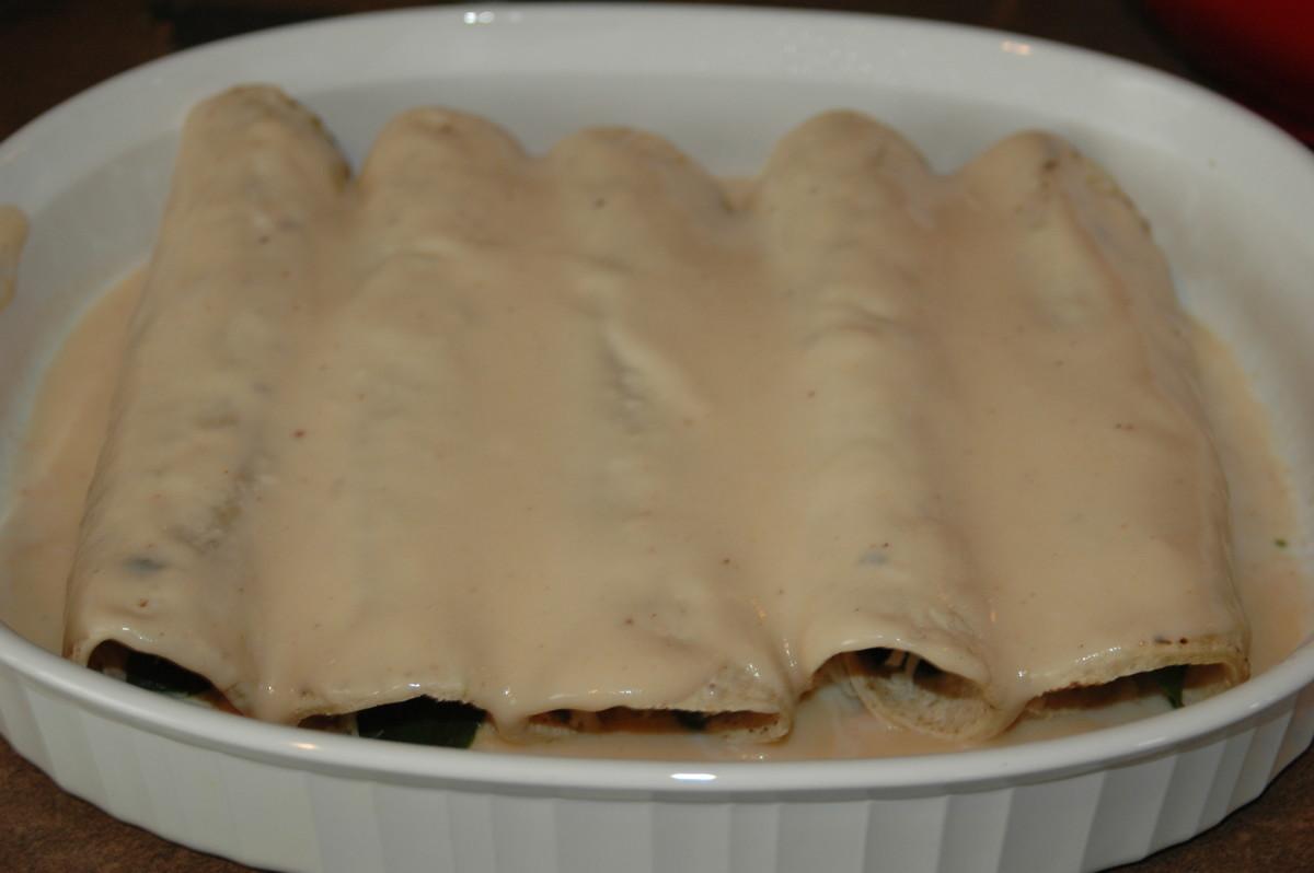 Ladle chipotle sauce over enchiladas