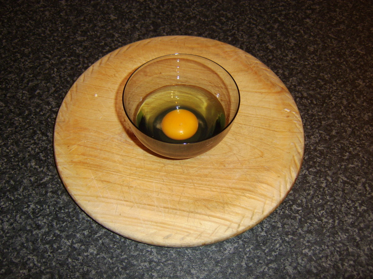 The egg is firstly broken into a small cup or bowl.