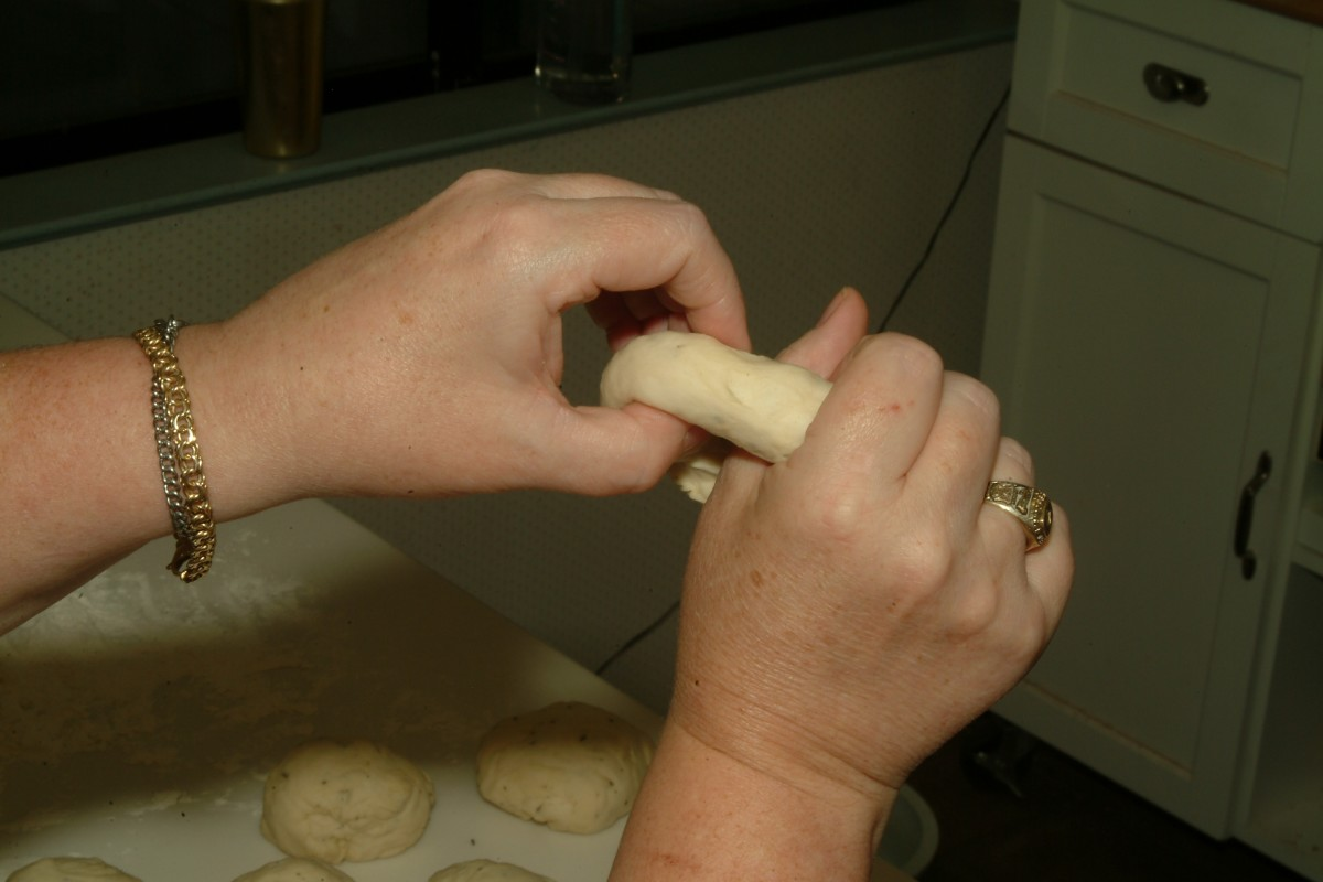 Form the bagel by gently turning and pulling the dough until a doughnut-like shape is achieved, about 2 - 3 inches across.