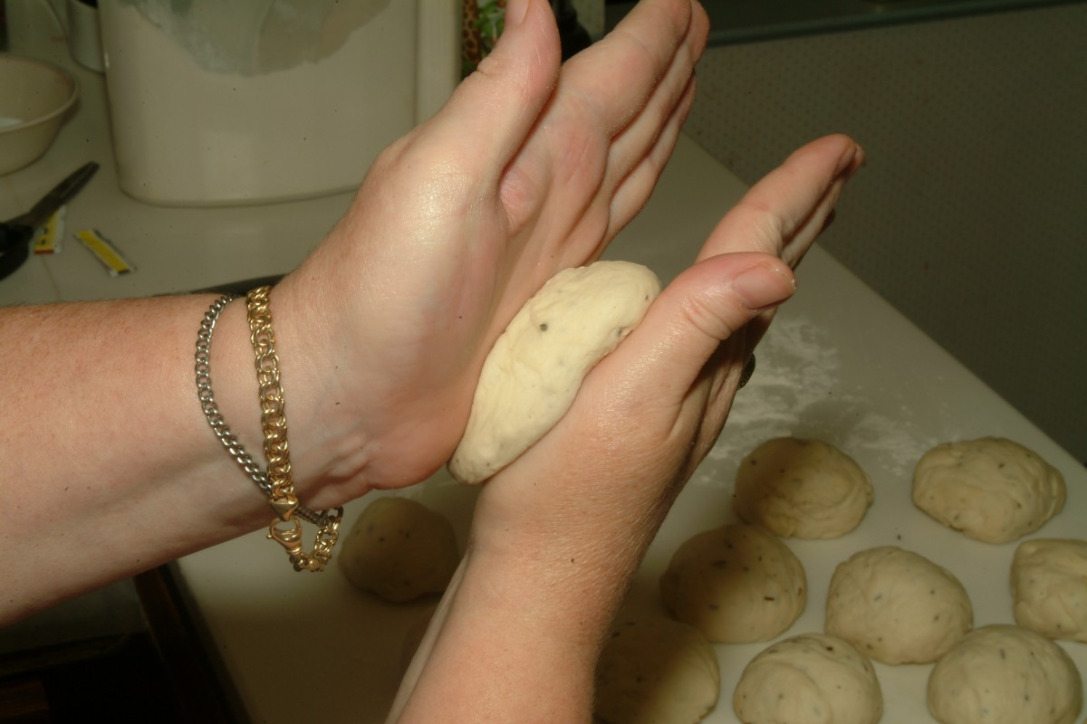 Firmly roll dough ball somewhat flat to press out extra air by moving your hands over dough ball while smoothing the surface.