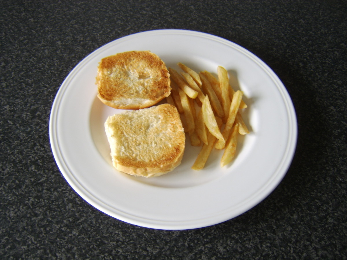 The toasted roll is plated with the fries, ready for the rested burger and garlic mayo.