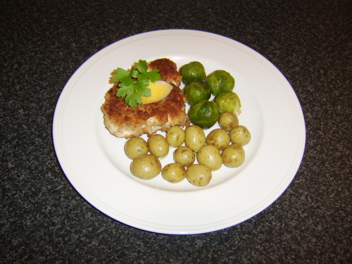 Schnitzel-style breaded turkey breast fillet is served with herb new potatoes and spiced Brussels sprouts.