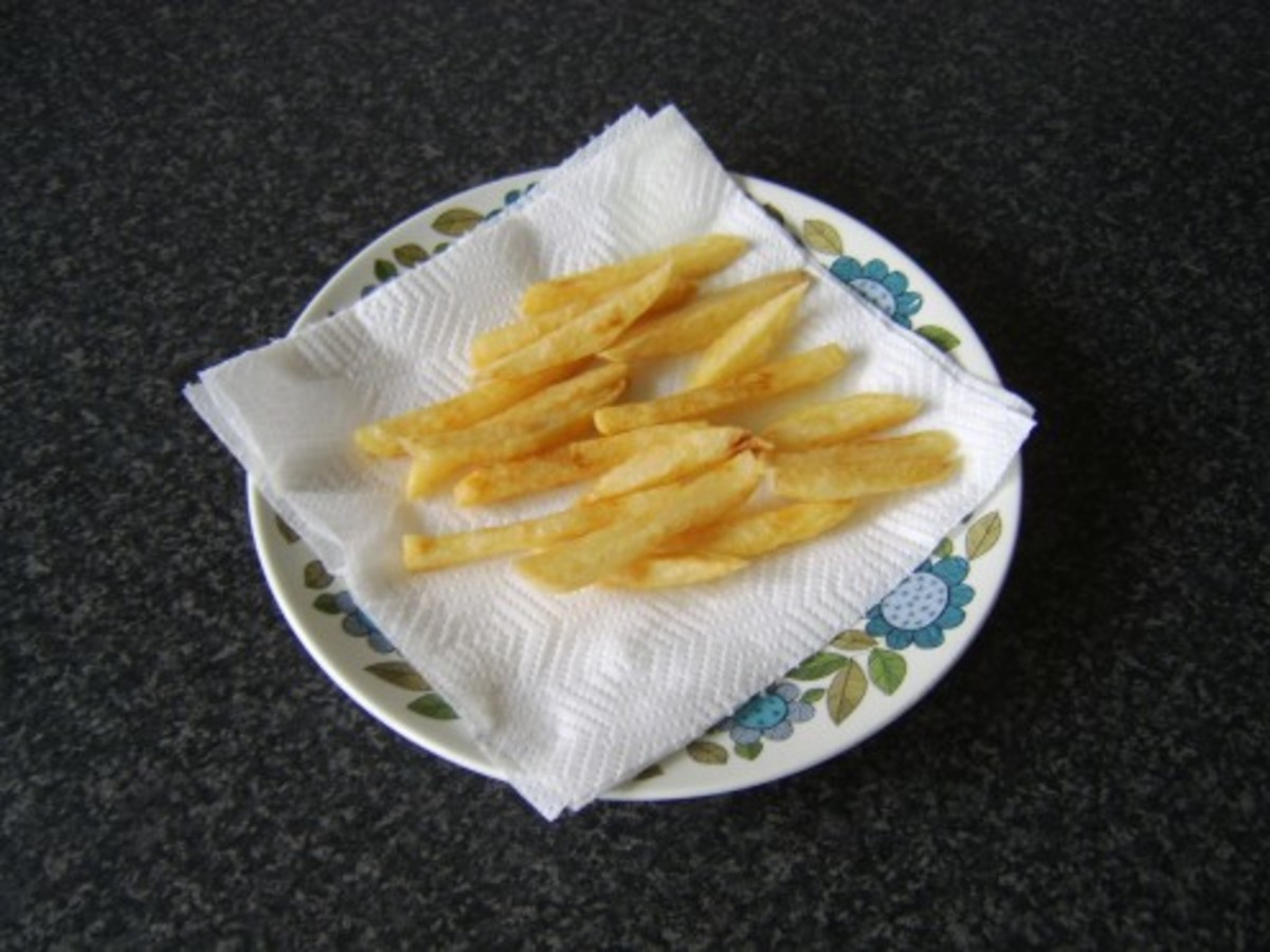 The fries are drained on kitchen paper after their final deep fry.
