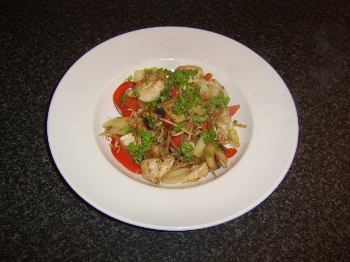 The turkey and vegetable stir fry is garnished with freshly chopped parsley prior to serving