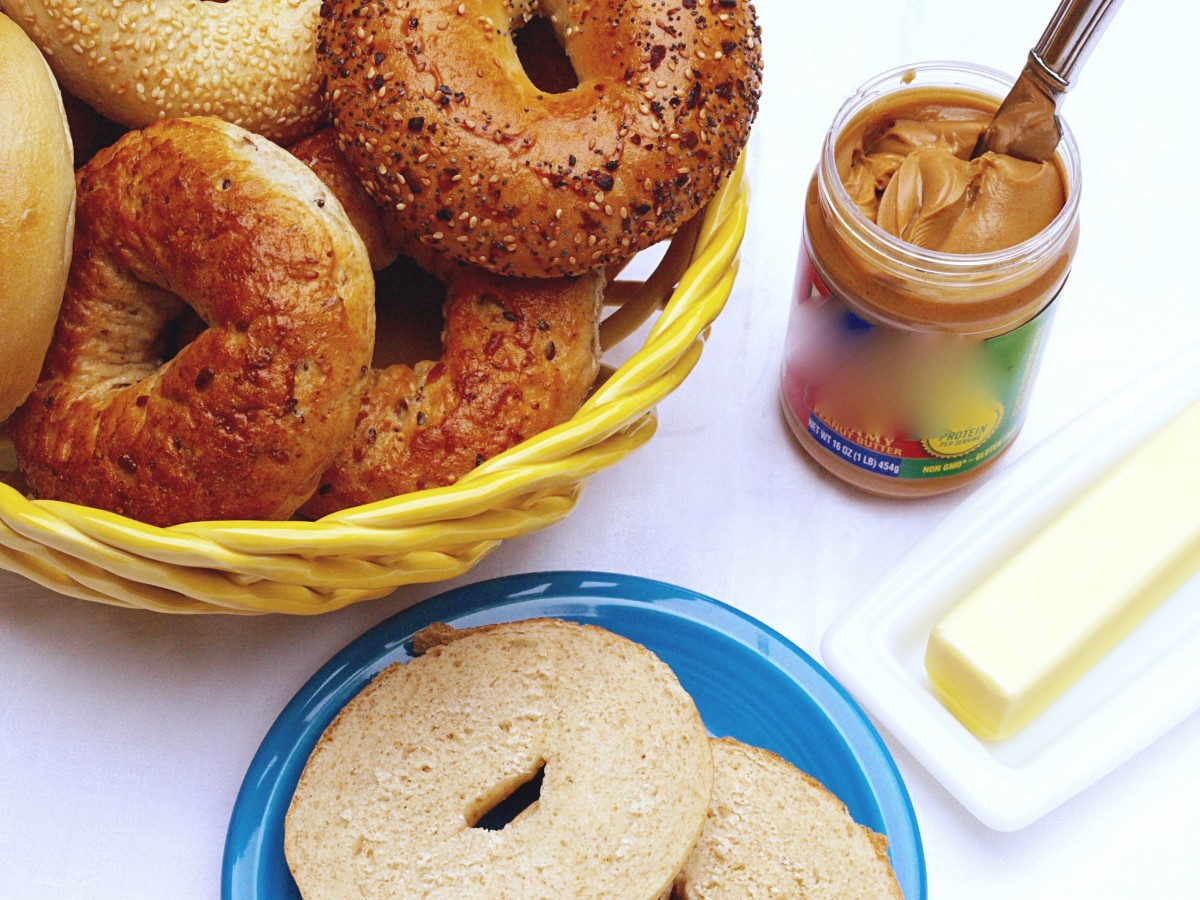 a basket of bagels and a sliced one on a plate