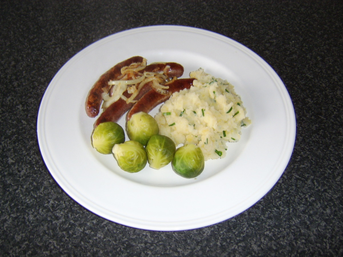 Clapshot served with pan fried sausages and onions and Brussels sprouts.