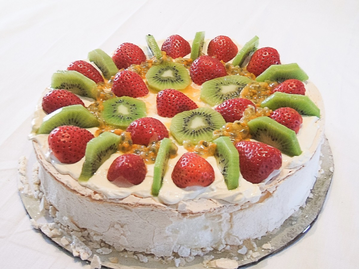 A pavlova dessert topped with strawberries, kiwi fruit and passion fruit