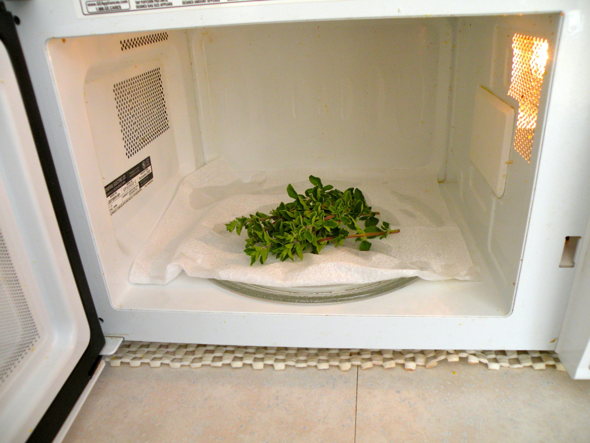 Place small bunch of herbs in the microwave on a paper plate- a paper napkin is a bad idea...