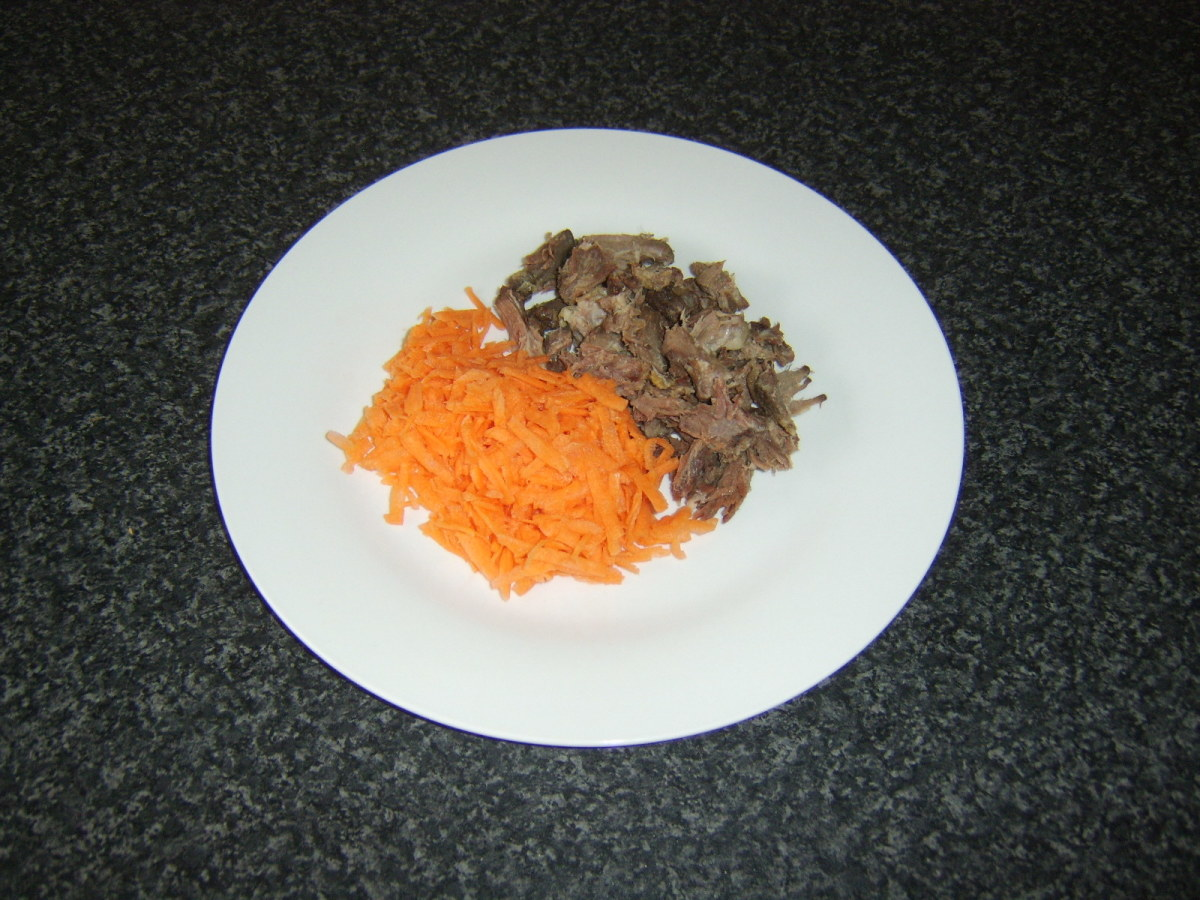 Grated carrot and meat pieces are added to soup