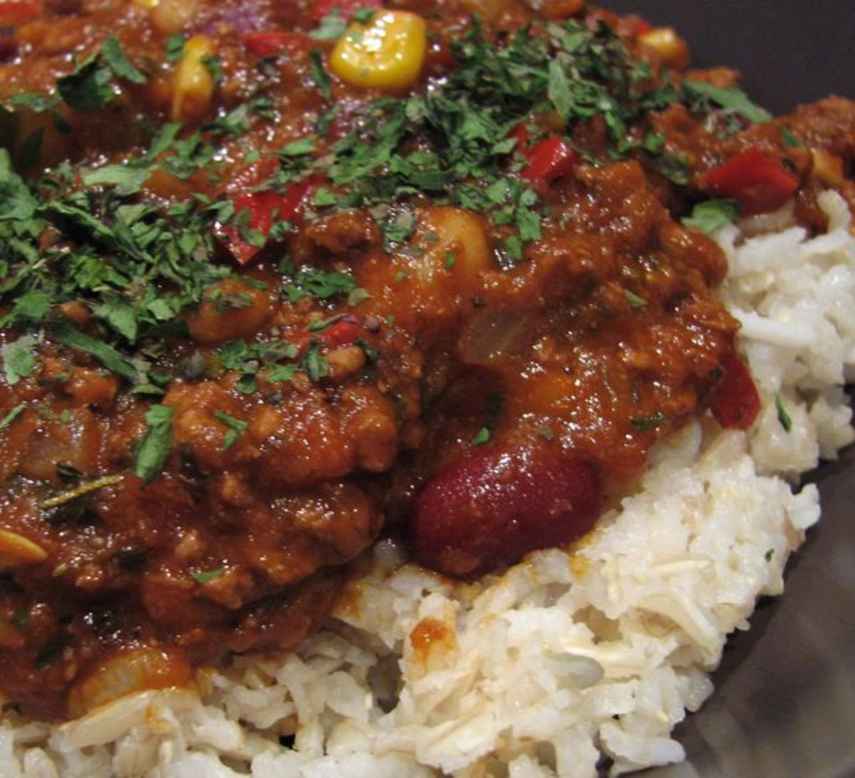 Mexican chili on rice, with corn, kidney and white beans, capsicum, carrot and cucumber.