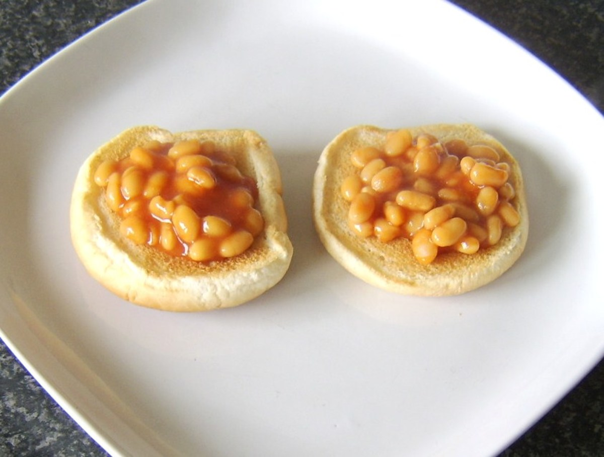 The beans are carefully spooned on to the toasted bread roll halves before adding the egg.