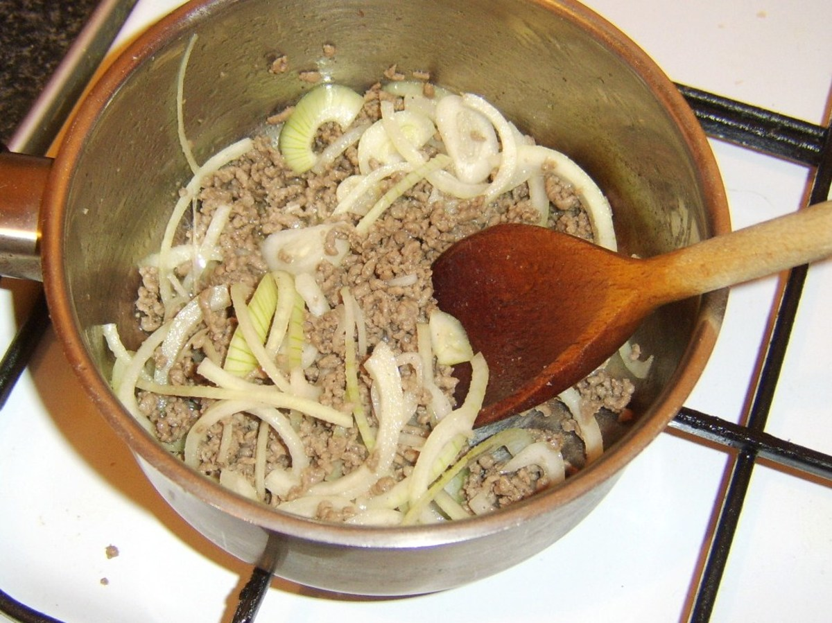 Sliced onion is stirred in to browned beef.