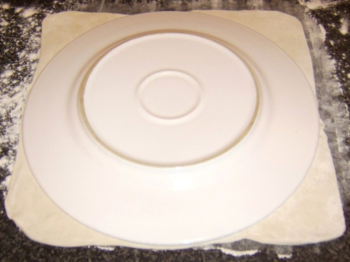 A large plate is used as a template for cutting the pastry.