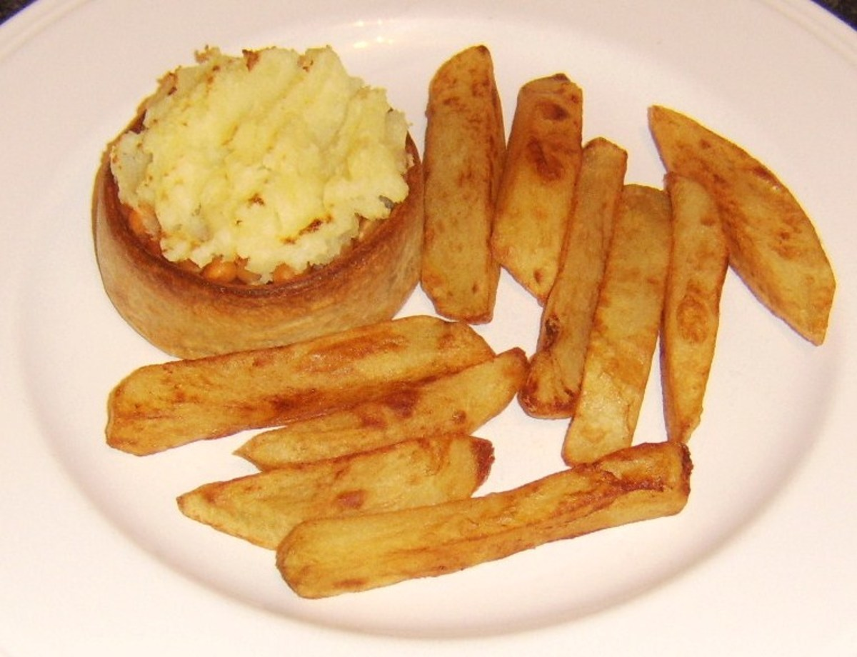 Scotch pie with baked beans and mash served with chips.