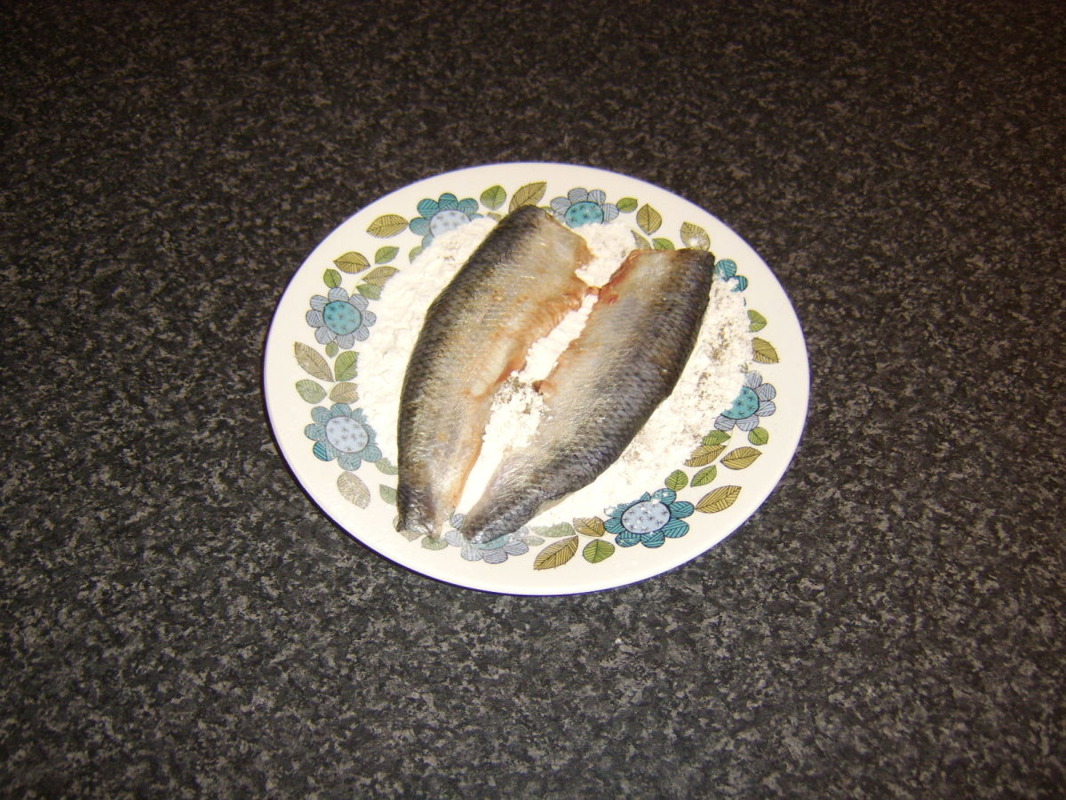 Herring fillets are floured for frying