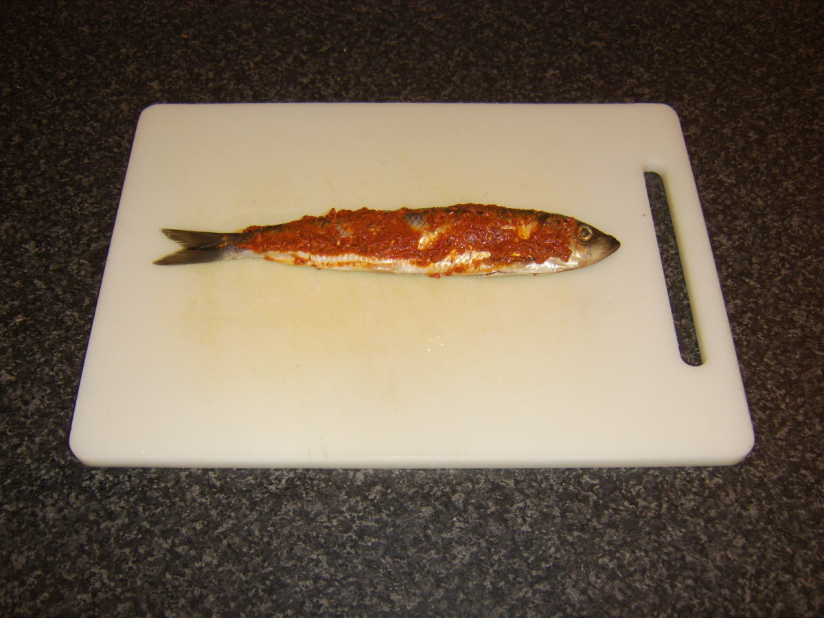 Red pesto sauce is spread on the herring