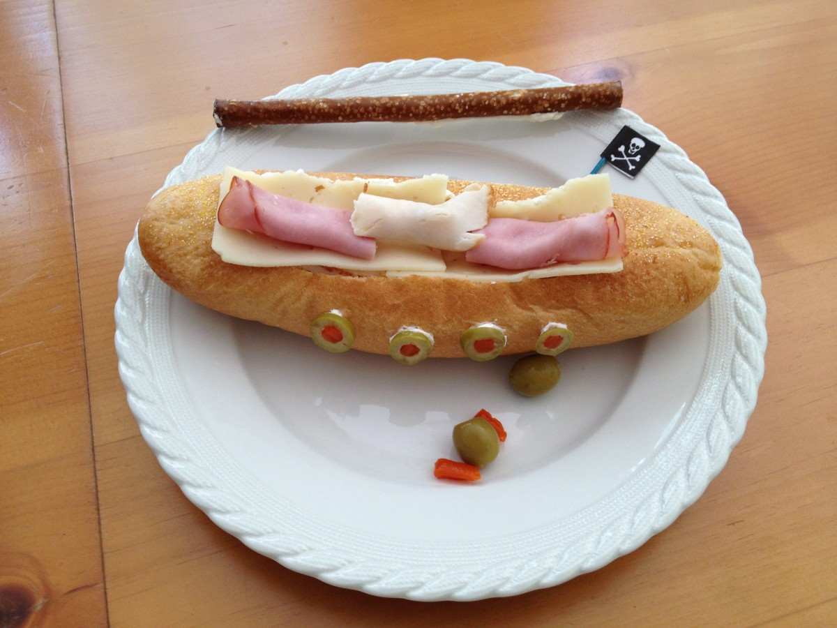 When it is time to eat, remove the toothpick pirate flag and set aside.  Place pretzel and olives to the side and add cheese slice to the sub.