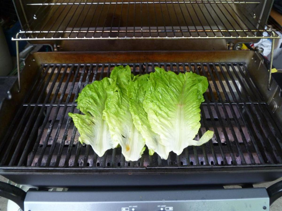 Overlap the wet romaine leaves on the grill.