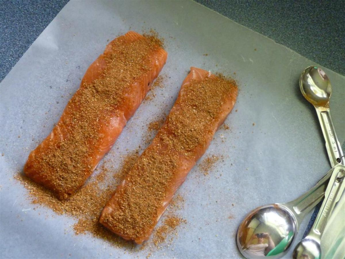Apply the dry rub seasoning in preparation for grilling.