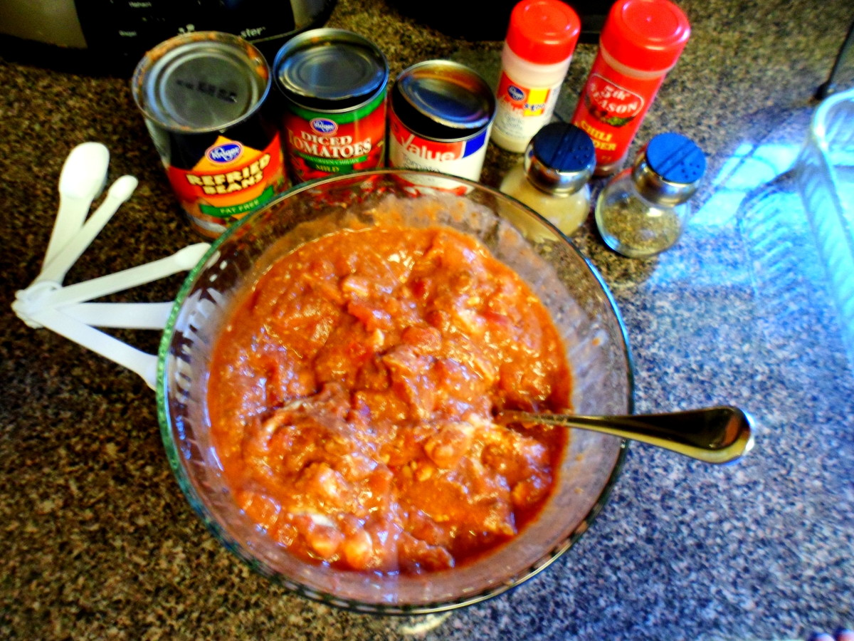 Mix together refried beans, tomatoes, tomato sauce, chicken, and spices in bowl.
