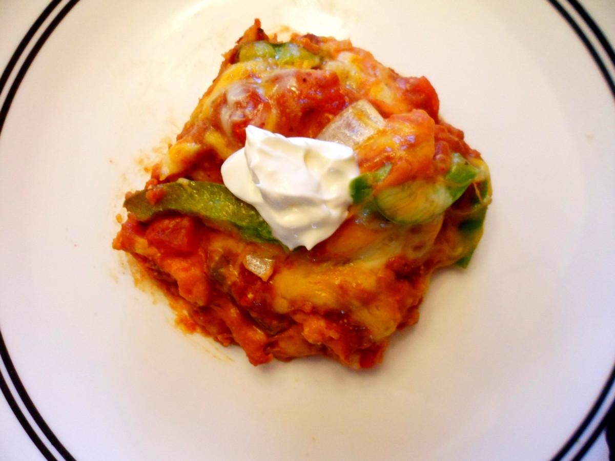 A serving of chicken fajita casserole with sour cream.