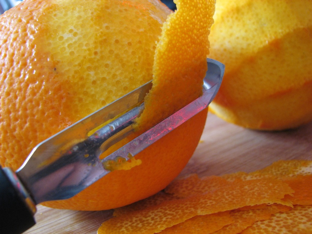 Peeling the oranges, avoiding the white pith.