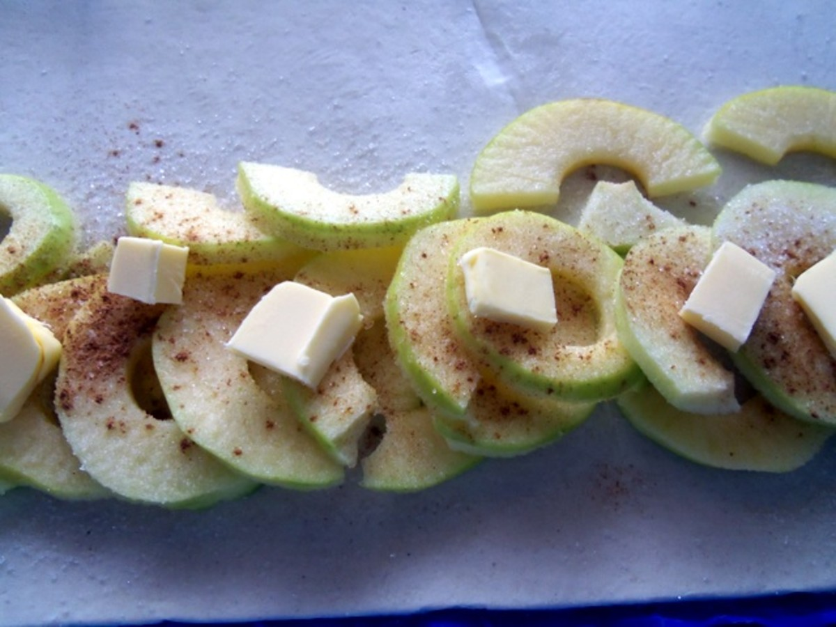 Lay out a row of apples and sprinkle with cinnamon and sugar. Add the cubes of butter.